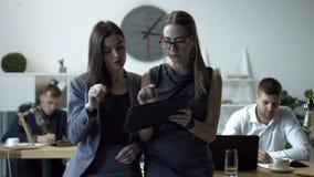 Säkra affärskvinnor som arbetar på den digitala minnestavlan lager videofilmer
