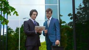 Säkra affärsmän framme av kontorsbyggnad Affärsman och hans kollega Packa ihop och finansmarknadbegrepp stock video