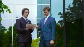 Säkra affärsmän framme av kontorsbyggnad Affärsman och hans kollega Packa ihop och finansmarknadbegrepp lager videofilmer