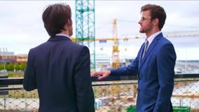 Säkra affärsmän som framme talar av modern kontorsbyggnad Affärsman och hans kollega Packa ihop och finansiellt arkivfilmer