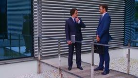 Säkra affärsmän som framme talar av modern kontorsbyggnad Affärsman och hans kollega Packa ihop och finansiellt stock video