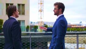 Säkra affärsmän som framme talar av modern kontorsbyggnad Affärsman och hans kollega Packa ihop och finansiellt lager videofilmer