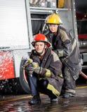 Säkra brandmän som besprutar vatten under övning Arkivfoto