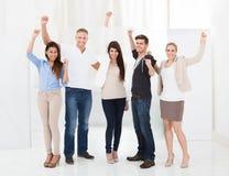 Säkra businesspeople som står med lyftta armar Arkivbild