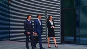 Säkra businesspersons som framme talar av modern kontorsbyggnad Affärsmän och affärskvinnan har affär arkivfilmer