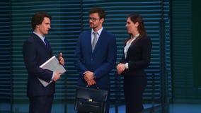 Säkra businesspersons som framme talar av modern kontorsbyggnad Affärsmän och affärskvinnan har affär stock video