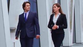 Säkra businesspersons som framme talar av modern kontorsbyggnad Affärsmän och affärskvinnan har affär lager videofilmer