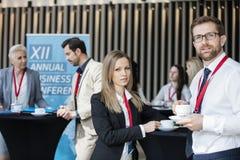 Säkra koppar för kaffe för affärsfolk hållande på lobbyen i konventcentrum royaltyfri bild