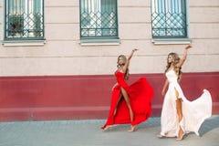 Säkra och trendiga flickor som upp stiger hennes eleganta aftonklänningar Arkivfoton
