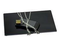 Säkra smartphonen och minnestavlan med en kedja som låsas med hänglåset Fotografering för Bildbyråer