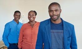 Säkra unga afrikanska coworkers som tillsammans står i ett kontor arkivbild
