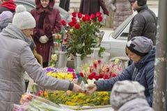 Sälja blommor på en tillfällig blomma marknadsför på helgdagsaftonen av internationella kvinnors dag Arkivbilder