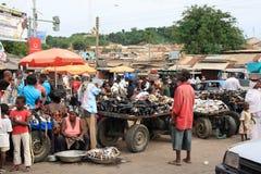 Sälja fisken och skor på afrikansk gatamarknad Arkivfoto