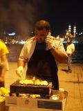 Sälja fisken på floden framme av en moské Royaltyfri Fotografi