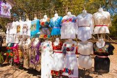 Sälja traditionell mexikankläder med blom- broderi och t-skjortor med skallen målade på gatamarknaden i Mexico royaltyfria bilder