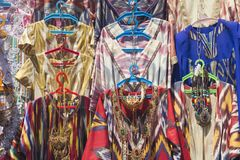Sälja traditionella orientaliska uzbekklänningar Handel med nationella dräkter Bukhara basar, Uzbekistan arkivfoton