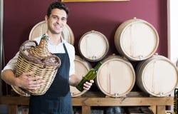 Säljare i förklädet som rymmer den stora vide- flaskan med vin i lager Arkivbilder