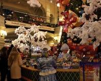Säljare i snöjungfrudräkterna bak räknaren på mässan för ` s för nytt år i det dekorerade GUMMIT royaltyfri fotografi