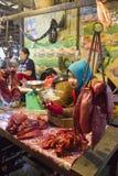 Säljare som spelar mobiltelefonen på Siem Reap Cambodja den våta marknaden Royaltyfri Foto