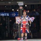 Säljaren bär likformign som symboliserar engelska som flaggan på ingången av shoppar kalla Britannia I bakgrund målade bilen i fä Arkivfoto