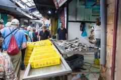 Säljaren erbjuder kunderna den nya fisken på marknaden i den gamla staden av tunnlandet i Israel Arkivfoton