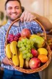 Säljaren föreslår för att köpa mogna frukter royaltyfri foto