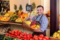 Säljaren föreslår för att köpa mogna frukter arkivfoton