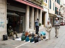 Säljaren fejkar märkta påsar som säljer påsar på den Venetian gatan royaltyfri foto