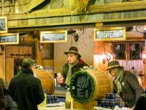 Säljaren häller varmt funderat vin på julmarknaden Arkivfoto