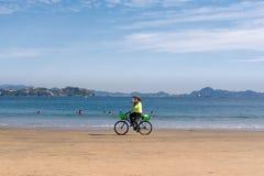 Säljaren med cykeln bär magasinet på stranden arkivfoto