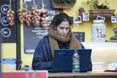 Säljaren på stadmarknad ser i datoren Royaltyfri Foto