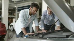 Säljaren visar motorn av den moderna automatiskn till en köpare i bilvisningslokal arkivfilmer