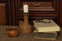 Sällsynt ljusstake med stearinljuset, den gamla lerakoppen, antika böcker och exponeringsglas på den woolen plädet mot bakgrund a royaltyfri foto