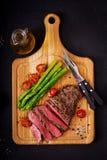 Sällsynt nötkött för saftig biff med kryddor på ett träbräde och en garnering av sparris arkivfoto