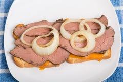 Sällsynt steknötkött och skivad löksmörgås på den vita plattan Royaltyfri Fotografi