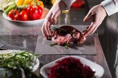 Sällsynta lamm som är klara för marinad med rosmarin Matlagning med brand i stekpanna Yrkesmässig kock i ett kök av royaltyfri fotografi