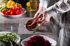 Sällsynta lamm som är klara för marinad med rosmarin Matlagning med brand i stekpanna Yrkesmässig kock i ett kök av arkivfoton