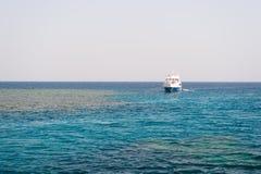 Sänd förankrat i det blåa havet på solig himmelhorisont Resa med havsfartyget Sommarsemester och rekreation Vattentransport och s Arkivbilder