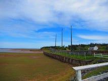 Sänd haveriet med 3 master längs shorelinen med ett hus i avståndet Arkivfoto