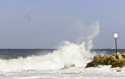 Sänd på en bakgrund av vågorna som bryter om en vågbrytare Royaltyfri Foto