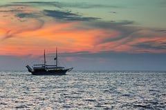 Sänd seglingen mot färgrik himmel efter solnedgång över havet Royaltyfria Foton