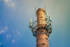 Sändare för mobil kommunikation på ett runt tegelstenrör mot fotografering för bildbyråer