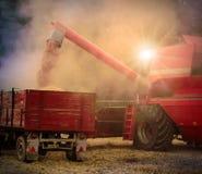 sändningen för lorryen för päfyllning för combinekornskörden lastar av vete Natt - arbete på bygd arkivfoton