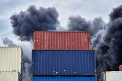 Sändnings av behållare som staplas i lagring med, putsar av svart giftlig rök från en brand mot en blå himmel royaltyfri foto
