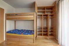 Säng för brits för barn` s med stort byggande-i garderob med öppna dörrar fotografering för bildbyråer