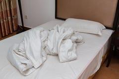 Säng i ett hotellrum med det uppvecklade täcket arkivbild