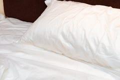Säng i hotellrum med det uppvecklade täcket i morgonen arkivfoto