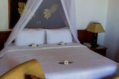 Säng i lyxig sovrumvilla royaltyfria foton