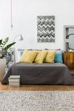 Säng med dekorativa gula kuddar Arkivbild