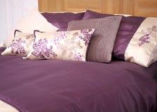 Säng med den purpurfärgade sängkläderuppsättningen Arkivbild